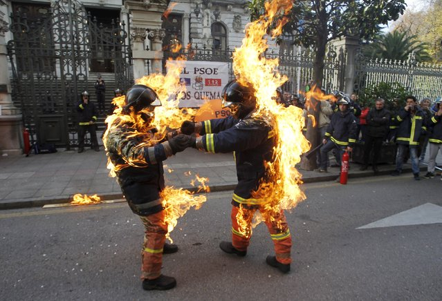 Firefighters demonstrate by lighting themselves on fire in front of a regional government building to demand more work safety measures and against what they say is a covert privatisation of their sector, in Oviedo, northern Spain, December 3, 2015. (Photo by Reuters/Stringer)