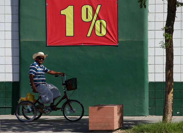 A man rides a tricycle past a grocery store in a town that borders Mexico, in San Luis Butter, California, United States, October 8, 2016. (Photo by Mike Blake/Reuters)
