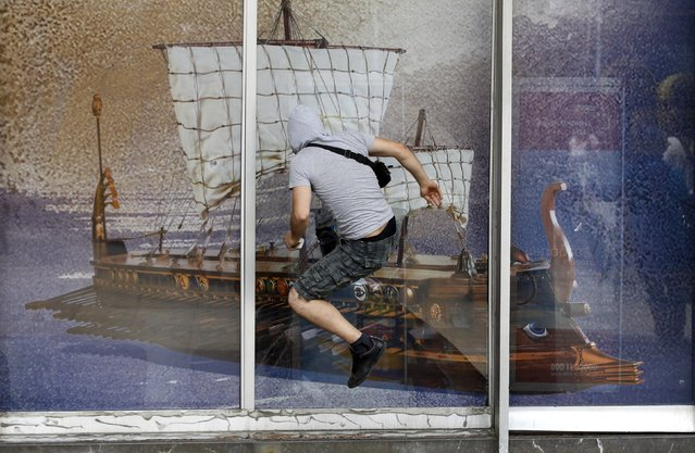 A demonstrator jumps to attempt to break a window displaying an image of an ancient greek galley during protests against austerity measures in Athens, in this June 28, 2011 file photo. (Photo by Yorgos Karahalis/Reuters)
