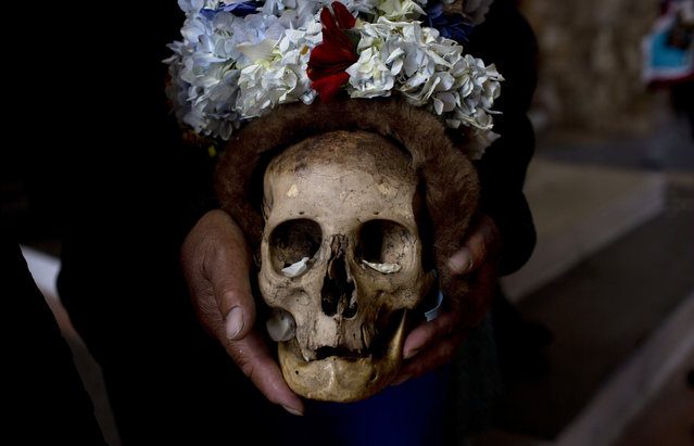 """A man holds a decorated human skull or """"natitas"""", after a blessing by the priest inside the Cementerio General chapel, during the Natitas Festival celebrations, in La Paz, Bolivia, Tuesday, November 8, 2016. (Photo by Juan Karita/AP Photo)"""