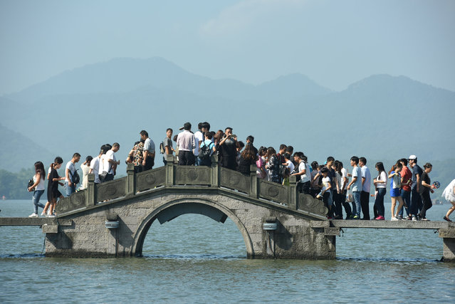 Visitors walk on a bridge on West Lake during China's golden week holiday in Hangzhou, Zhejiang Province, China, October 2, 2016. (Photo by Reuters/Stringer)