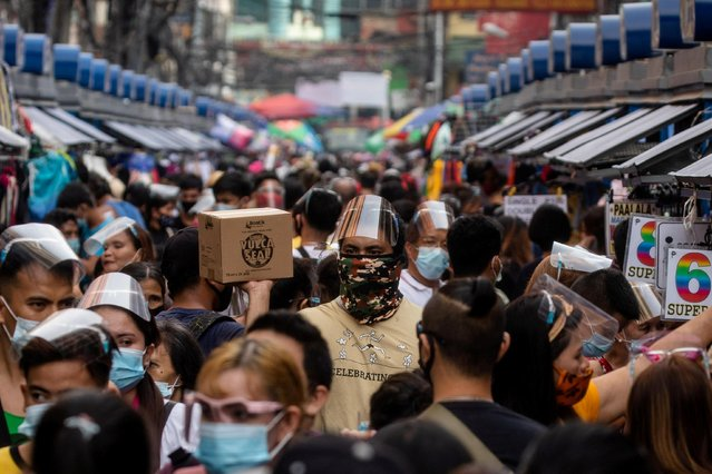 Filipinos wearing masks and face shields for protection against the coronavirus disease (COVID-19) walk along a street market in Manila, Philippines, December 3, 2020. (Photo by Eloisa Lopez/Reuters)