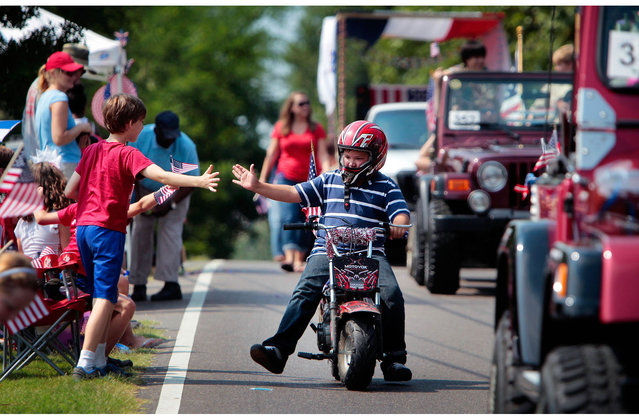 Patrick Ardis, 10, gets a high-five from his friend Porter Rosenberg, 10, left, while riding in the Cordova Independence Day Parade at the Cordova Community Center in Cordova, Tenn., on Thursday, July 4, 2013.  (Photo by Jim Weber/AP Photo/The Commercial Appeal)