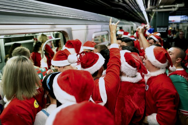 Revelers dressed in Santa Claus and other holiday themed outfits wait for the subway during the annual SantaCon event in the Brooklyn borough of New York, December 12, 2015. (Photo by Brendan McDermid/Reuters)