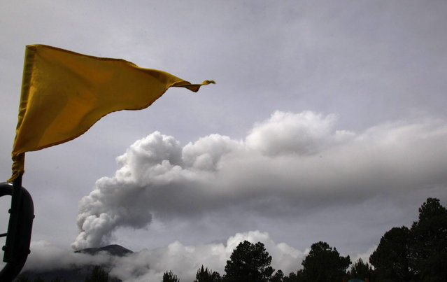 A Stage 3 Yellow flag flies in the Paso de Cortes area near Popocatepetl volcano, behind left, in Mexico, Monday, July 8, 2013. Mexico's National Center for Disaster Prevention raised the volcano alert to Stage 3 Yellow, the final step before a Red alert, when possible evacuations could be ordered. A Stage 3 Yellow alert had been in effect during eruptions earlier this year until early June, when it was lowered. (Photo by Marco Ugarte/AP Photo)