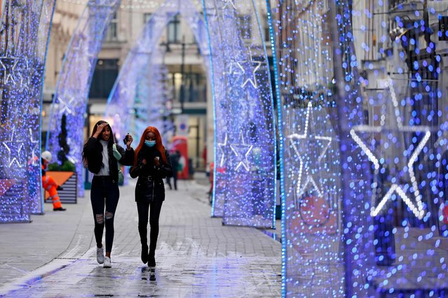 "Pedestrians, one wearing a protective face covering to combat the spread of the coronavirus, walk past Christmas decorations in a street in central London on November 27, 2020, as life under a second lockdown continues in England. England will return to a regional tiered system when the national stay-at-home order ends on December 2, and 23.3 million residents in the worst-hit areas are set to enter the ""very high"" alert level. (Photo by Tolga Akmen/AFP)"