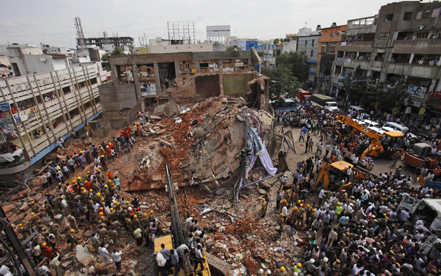 Indians watch as Indian Fire officials and rescue workers look for survivors at the site of a collapsed building, in Hyderabad, India, Monday, July 8, 2013. An official said at least ten people have been killed and 12 others injured after a two-story hotel collapsed in southern India (Photo by Mahesh Kumar A./AP Photo)