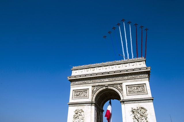 French elite flying team Patrouille de France jets fly over the Arch of Triumph on the Place de l'Etoile on July 14, 2013 during the Bastille Day, the French National Day, parade in Paris. (Photo by Etienne Laurent/AFP Photo)