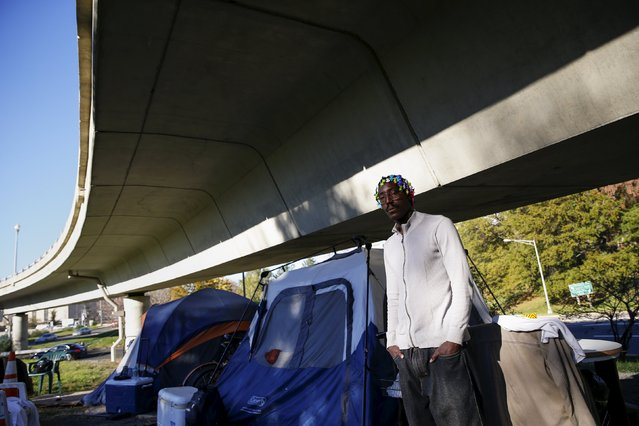 "James Bannister, 38, stands by his tent near the Watergate and Whitehurst Freeway in Washington D.C., November 16, 2015. ""Tent city is the idea that you can be in a place that is peaceful and quiet and away from everybody else, where you don't have any violence, no problems or none of the above. I'm on the list for housing but have been on the list for 20 years"", Bannister said. (Photo by Shannon Stapleton/Reuters)"
