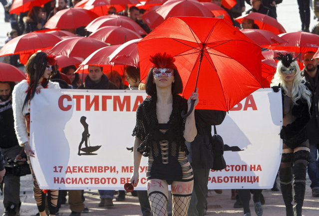 People carrying red umbrellas march through downtown Skopje, Macedonia, marking the International Day to End Violence against s*x Workers, Thursday, December 17, 2015. A group of s*x workers, supported by members of non-government organizations, rallied Thursday demanding rights for the s*x workers and destigmatization of their profession. The banner reads: The Stigma Kills. (Photo by Boris Grdanoski/AP Photo)