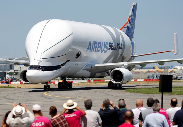 "People take pictures as an Airbus Beluga XL transport plane lands during its first flight event in Colomiers near Toulouse, France, July 19, 2018. Airbus employees were asked to vote on possible designs for the craft, which ended up being painted to resemble a cartoon cetacean. ""The six designs we proposed for consideration by employees respected our brand identity while running from the conventional to the unconventional, even adding a touch of fun"", said Tim Orr, head of branding at Airbus. (Photo by Regis Duvignau/Reuters)"
