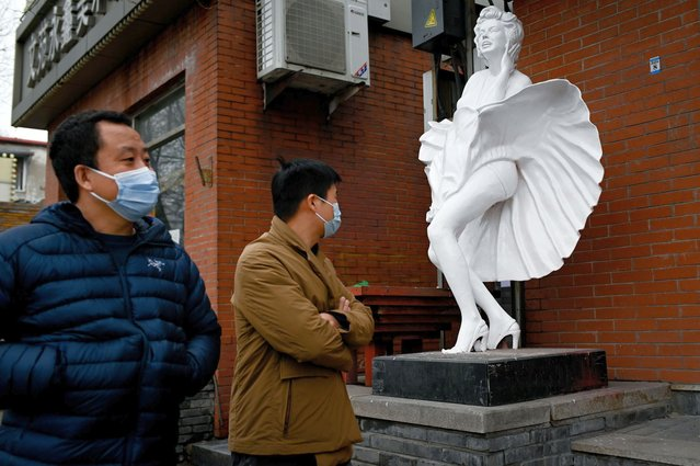 A man looks at a figure outside a store as he walks along a street in Beijing on March 2, 2021. (Photo by Wang Zhao/AFP Photo)
