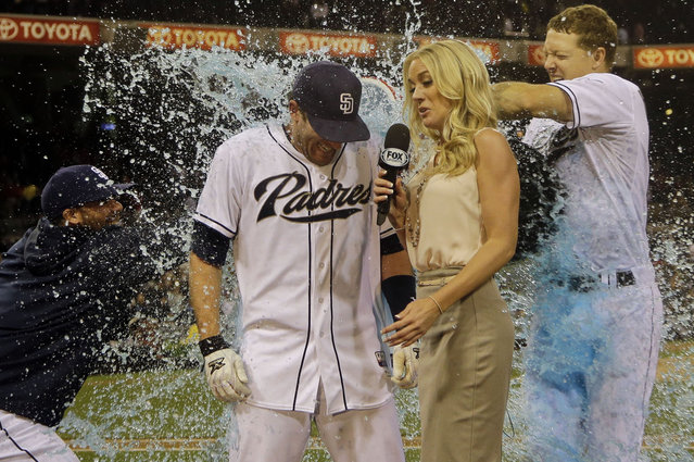 San Diego Padres' Chris Denorfia gets the victory bath from Nick Hundley, right, and Rene Rivera while being interviewed by television reporter Kelly Crull after his two-run walk off home run in the bottom of the ninth inning gave the Padres a 2-1 victory over the Cincinnati Reds in a baseball game in San Diego, Monday, July 29, 2013. (Photo by Lenny Ignelzi/AP Photo)
