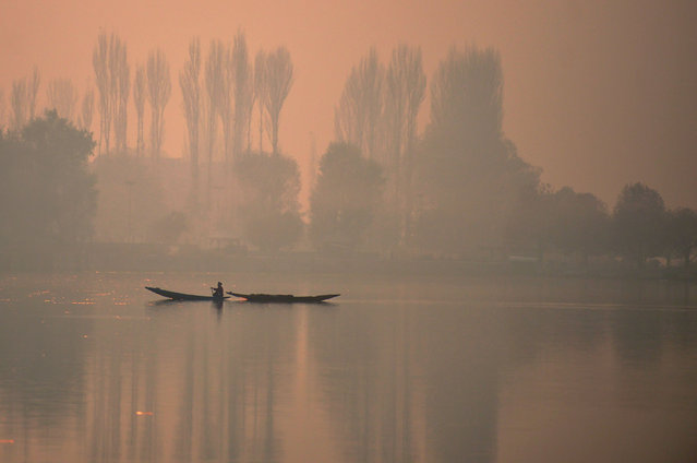 An Indian Kashmiri fisherman rows his boat on Dal Lake in dense fog in Srinagar on November 18, 2016 Air traffic is badly affected in Kashmir due to dense fog that forced cancellation of all flights. (Photo by Tauseef Mustafa/AFP Photo)