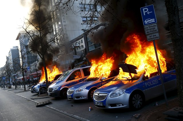 Four German police cars set on fire by anti-capitalist protesters burn near the European Central Bank (ECB) building hours before the official opening of its new headquarters in Frankfurt, Germany March 18, 2015. (Photo by Kai Pfaffenbach/Reuters)