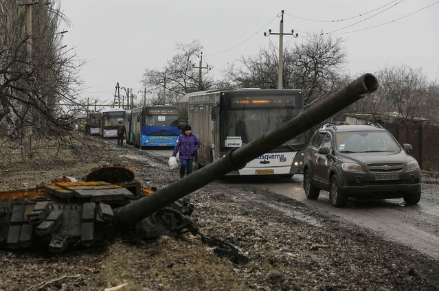 Empty buses, intended for internally displaced persons (IDPs), wait along a road beside a burnt-out tank turret while travelling in the direction of the village of Debaltseve to evacuate the residents, in Vuhlehirsk, Donetsk region  February 6, 2015. (Photo by Maxim Shemetov/Reuters)