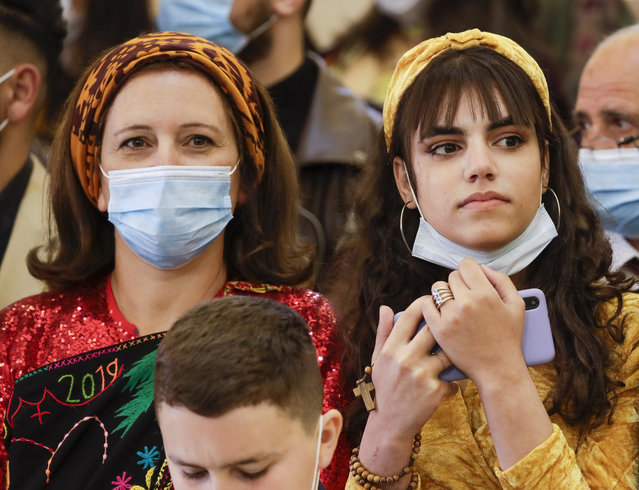 Faithful wait for Pope Francis to arrive at a meeting with the Qaraqosh community at the Church of the Immaculate Conception, in Qaraqosh, Iraq, Sunday, March 7, 2021. (Photo by Andrew Medichini/AP Photo)