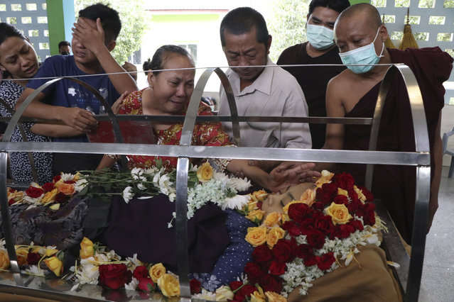 Friends and relatives mourn over the body of Ma Su Su Kyi, a 32 year old South Korean bank employee, who died from gunshot wounds Friday, April 2, 2021, Yangon, Myanmar. South Korean Shinhan Bank spokesman said it temporary closed its branch in Yangon and was considering bringing its South Korean employees back home after its Myanmar employee Ma Su Su Kyi was fatally shot by security forces. (Photo by AP Photo/Stringer)