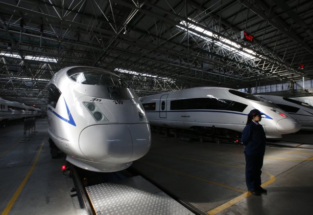 An employee stands next to high speed railway model CRH380B trains at a production line of its parts at China CNR's Tangshan Railway Vehicle's factory in Tangshan, Hebei province, February 11, 2015. (Photo by Kim Kyung-Hoon/Reuters)