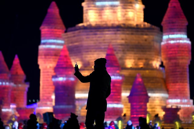 A man takes a photo in front of ice sculptures at the China Ice and Snow World on eve of the opening ceremony of the Harbin International Ice and Snow Festival in Harbin, northeast China's Heilongjiang province on January 4, 2016. Over one million visitors are expected to attend the spectacular Harbin Ice Festival, where buildings of ice are bathed in ethereal lights and international ice sculptors compete for honours. (Photo by Wang Zhao/AFP Photo)