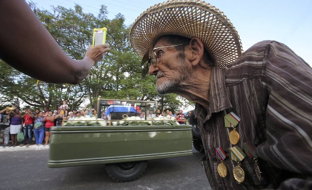 Guillermo Enrique Cadiz, 82, who fought with Fidel Castro in the Sierra Maestra, watches as Castro's ashes pass him during a three-day journey to the eastern city of Santiago, in Jovellanos, Cuba, November 30, 2016. (Photo by Carlos Garcia Rawlins/Reuters)