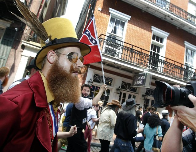 Jeffrey Moustache keeps eyes straight ahead as a photographer singles him out during a parade through the French Quarter kicking off the fourth annual Just For Men National Beard and Moustache Championships Saturday, September 7, 2013 in New Orleans. Moustache was competing in the Verdi division. Contestants competed in 18 different categories including Dali, full beard natural and sideburns. (Photo by Susan Poag/AP Photo)