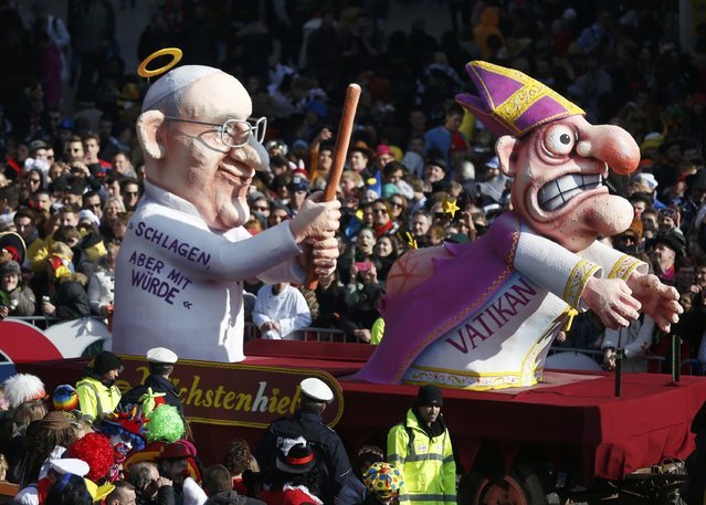 A carnival float with a papier-mache caricature drives past revellers during the traditional Rose Monday carnival parade in the western German city of Duesseldorf February 16, 2015. (Photo by Ina Fassbender/Reuters)
