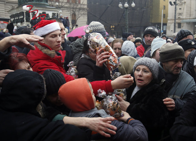 People gather to receive a piece of traditional Christmas bread to mark the Orthodox Christmas Day festivities in Belgrade, Serbia, Wednesday, January 7, 2016. (Photo by Darko Vojinovic/AP Photo)