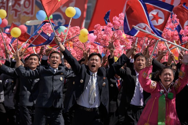 Participants wave flowers as they march past a balcony from where North Korea' s leader Kim Jong Un was watching, during a mass rally on Kim Il Sung square in Pyongyang on September 9, 2018. (Photo by Ed Jones/AFP Photo)