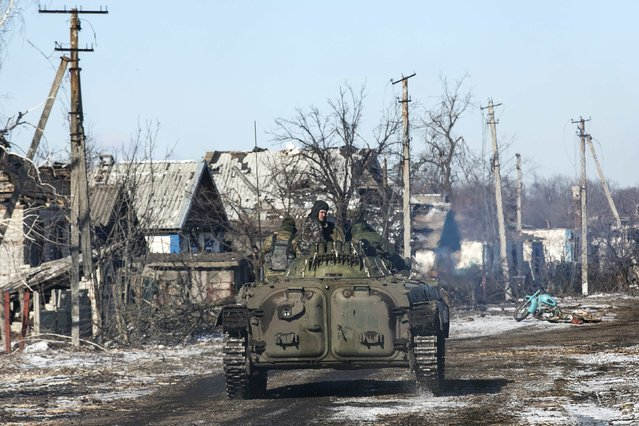 Fighters with separatist self-proclaimed Donetsk People's Republic army ride atop a moving armoured personnel carrier in the village of Nikishine, south east of Debaltsev February 17, 2015. (Photo by Baz Ratner/Reuters)