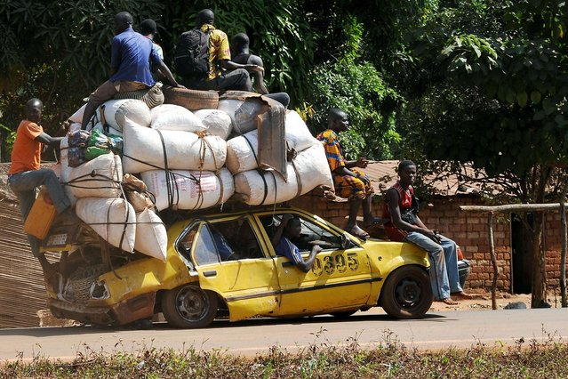 This car deserves a medal for heroism, the picture shows a group of people fleeing a town in CAR (Central Africa Republic). (Photo by AFP Photo/Getty Images)