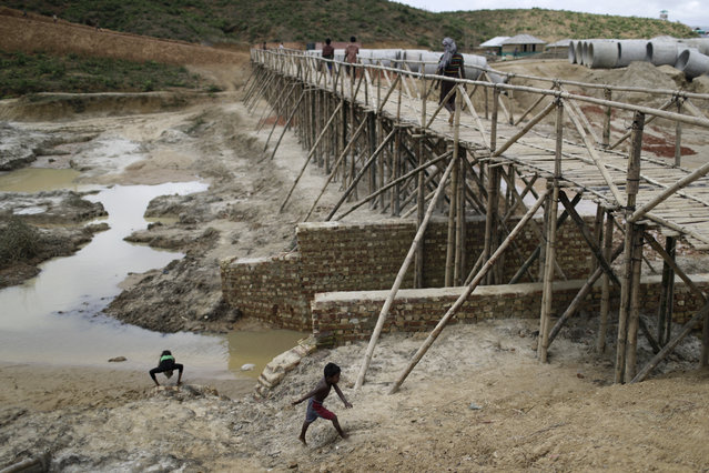 In this June 28, 2018, photo, Rohingya refugees cross a newly built bridge in the extended area of Kutupalong refugee camp in Bangladesh where some refugees living in areas considered at risk of landslides and flooding were relocated to. (Photo by Wong Maye-E/AP Photo)