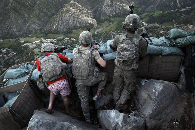 """Soldiers from the U.S. Army First Battalion, 26th Infantry take defensive positions at firebase Restrepo after receiving fire from Taliban positions in the Korengal Valley of Afghanistan's Kunar Province on May 11, 2009. Spc. Zachary Boyd of Fort Worth, TX, far left was wearing """"I love NY"""" boxer shorts after rushing from his sleeping quarters to join his fellow platoon members. From far right is Spc. Cecil Montgomery of Many, LA and Jordan Custer of Spokan, WA, center. (Photo by David Guttenfelder/AP Photo/File)"""