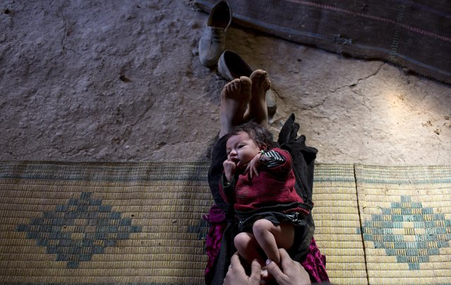 Bari Moumouch, a 20-year-old Berber mother, plays with her new born child in the village of Ait Sghir in the High Atlas region of Morocco February 14, 2015. (Photo by Youssef Boudlal/Reuters)