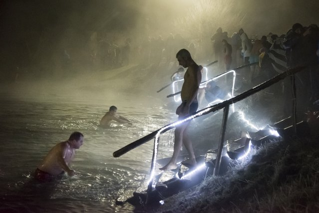 Russian Orthodox believers bathe in ice water in a pond to mark Epiphany outside Simferopol, Crimea, Tuesday, January 19, 2016. Water that is blessed by a cleric on Epiphany is considered holy and pure until next year's celebration, and is believed to have special powers of protection and healing. The Russian Orthodox Church follows the old Julian calendar, according to which Epiphany falls on Jan. 19.  (Photo by Denis Tyrin/AP Photo)