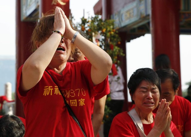 Chinese relatives of passengers aboard missing Malaysia Airlines flight MH370 pray at the Thean Hou temple in Kuala Lumpur, March 1, 2015. March 8 will mark the 1 year anniversary since the Boeing 777 disappeared shortly after taking off from Kuala Lumpur, bound for Beijing, carrying 239 passengers and crew. Families from China have been in Malaysia to demand answers from the Malaysian government about the whereabouts of the aircraft.  REUTERS/Olivia Harris