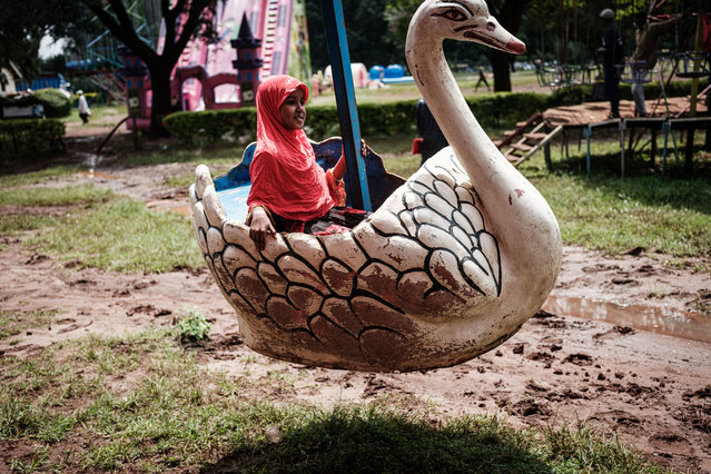 A muslim girl rides on a swan at an amusement park after attending the Eid Al-Fitr prayer that marks the end of the Holy month of Ramadan at Uhuru Park in Nairobi, Kenya, on May 13, 2021. (Photo by Yasuyoshi Chiba/AFP Photo)