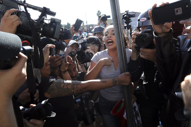 "An anti-migrant demonstrator is surrounded by the press as she argues with a woman during a protest against the presence of thousands of Central American migrants in Tijuana, Mexico, Sunday, November 18, 2018. Protesters accused the migrants of being messy, ungrateful and a danger to Tijuana; complained about how the caravan forced its way into Mexico, calling it an ""invasion"", and voiced worries that their taxes might be spent to care for the group as they wait possibly months to apply for U.S. asylum. (Photo by Rodrigo Abd/AP Photo)"