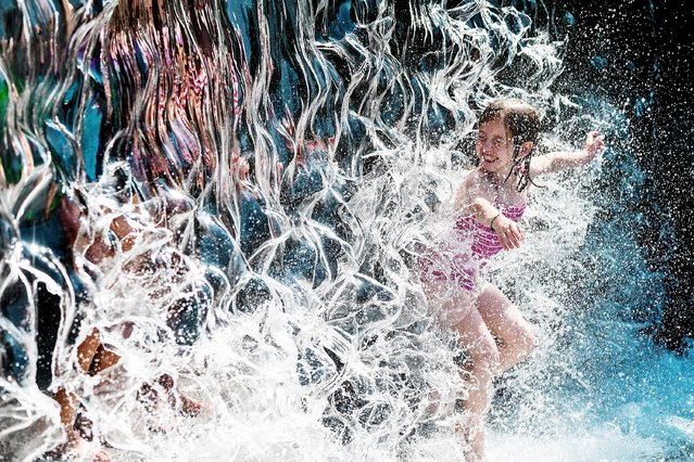 A young girl splashes through a waterfall at a park in Washington, DC, on June 28, 2021, as a heatwave moves over much of the United States. Swathes of the United States and Canada endured record-setting heat on June 27, 2021, forcing schools and Covid-19 testing centers to close and the postponement of an Olympic athletics qualifying event, with forecasters warning of worse to come. The village of Lytton in British Columbia broke the record for Canada's all-time high, with a temperature of 46.6 degrees Celsius (116 Fahrenheit), said Environment Canada. (Photo by Jim Watson/AFP Photo)