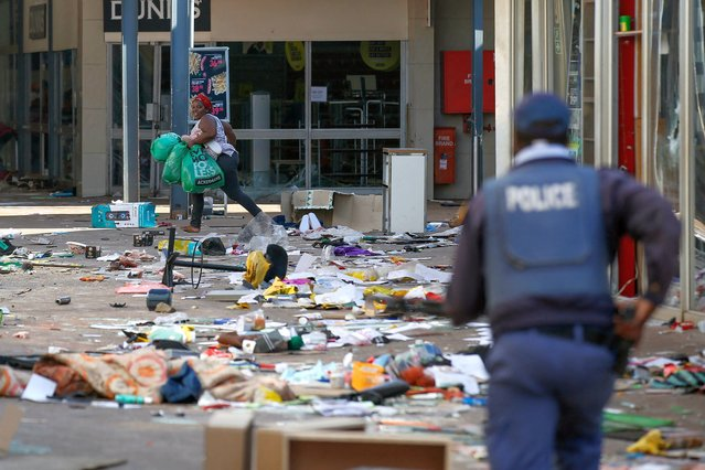 A looter smiles as she runs away from a member of the South African Police Services (SAPS) inside the Lotsoho Mall in Katlehong township, East of Johannesburg, on July 12, 2021. Several shops are damaged and cars burnt in Johannesburg, following a night of violence. Police are on the scene trying to control further protests. It is unclear if this is linked to sporadic protests following the incarceration of former president Jacob Zuma. (Photo by Phill Magakoe/AFP Photo)