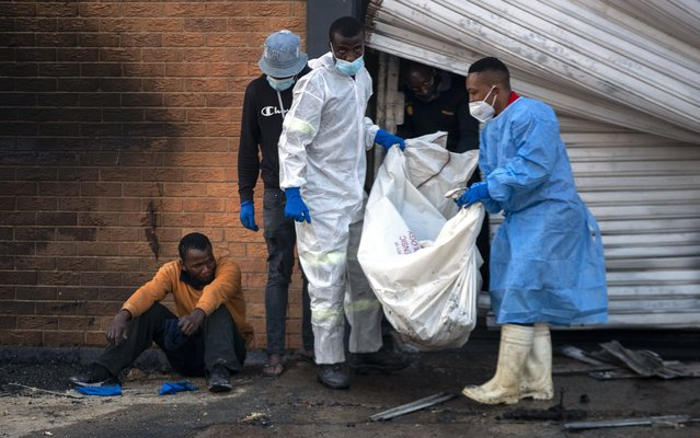 A family member watches on as police forensics officers carry the body his brother who was found inside a burned shop, in Johannesburg, South Africa, Sunday, July 11, 2021. Protests have spread from the KwaZulu Natal province to Johannesburg against the imprisonment of former South African President Jacob Zuma who was imprisoned last week for contempt of court. (Photo by Themba Hadebe/AP Photo)