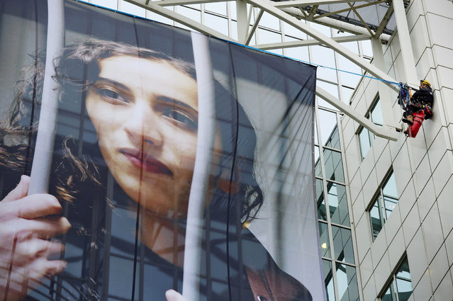 """Members of Greenpeace hang a large poster of Dutch activist Faiza Oulahsen on the office building of Shell during a protest calling for the release of the """"Arctic 30"""" in Rotterdam on November 21, 2013. Russia arrested Oulahsen along with 29 other crew members of the Arctic Sunrise after activists in September scaled an oil rig in the Barents Sea owned by energy giant Gazprom. (Photo by Martijn Beekman/AFP Photo/ANP)"""