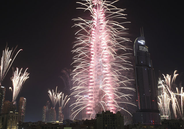 Fireworks explode at the Burj Khalifa, the world's tallest building, and surrounding skyscrapers to mark New Year in Dubai, United Arab Emirates, on Sunday, January 1, 2017. (Photo by Jon Gambrell/AP Photo)