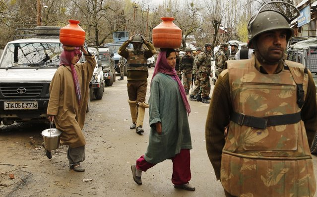 Kashmiri women carry pots filled with drinking water on their heads and walk past security officers standing guard during a gunbattle at Hardshoora village, 35 kilometers (20 miles) north of Srinagar, India, Thursday, April 2, 2015. Suspected Kashmiri rebels and Indian security personnel were engaged in a fierce gunbattle Thursday in the Himalayan territory, officials said. (Photo by Mukhtar Khan/AP Photo)