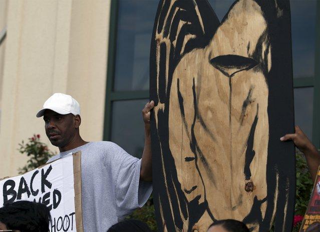 Jerome Taylor of North Charleston, South Carolina holds signs at a rally in North Charleston, South Carolina April 8, 2015. (Photo by Randall Hill/Reuters)