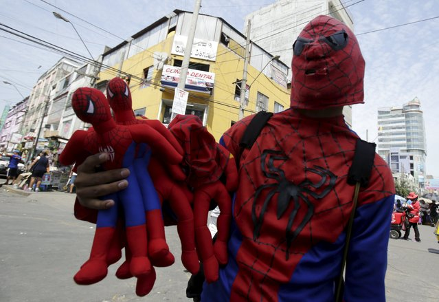 Fabian, wearing a Spider-Man costume, sells toys in the commercial zone of Gamarra in Lima, April 16, 2015. Gamarra, located in the central district of La Victoria, is home to the largest textile industry in Lima and has several shops and malls where all kinds of clothing are made. There are more than 10,000 entrepreneurs and 17,000 stores housed in the 20 blocks in the district, according to local media. (Photo by Mariana Bazo/Reuters)