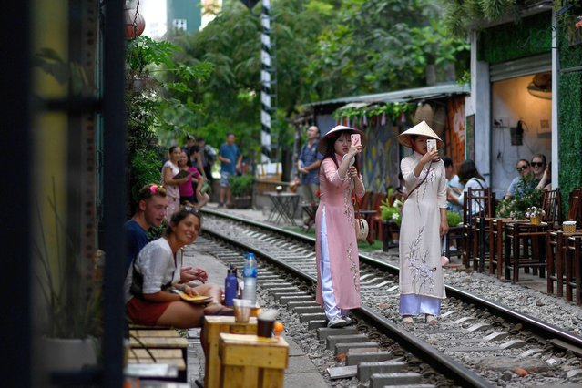 This photograph taken on June 9, 2019 shows women posing for a selfie on the railway track in Hanoi's popular train street. (Photo by Manan Vatsyayana/AFP Photo)
