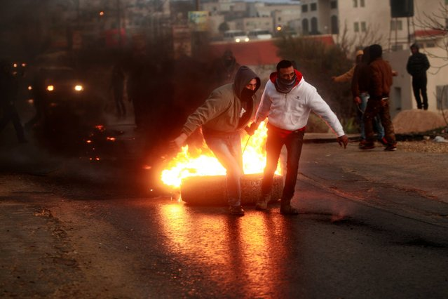 Palestinians drag a burning tire during clashes with Israeli soldiers at a protest against the expansion of the nearby Jewish settlement Ofra outside the village of Silwad, near the West Bank city of Ramallah, Friday, January 10, 2014. (Photo by Majdi Mohammed/AP Photo)