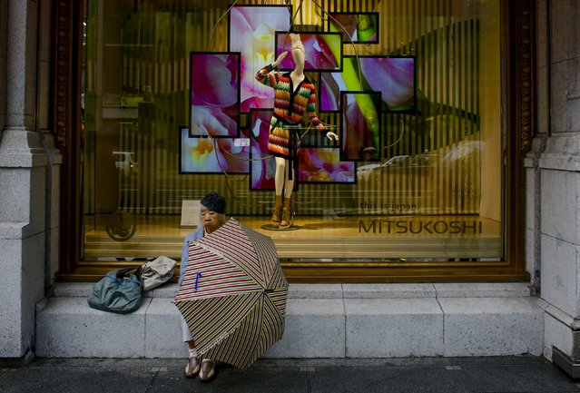 A woman shelters from the rain in front of a luxury department store in Tokyo, in this February 18, 2015 file photo. (Photo by Thomas Peter/Reuters)