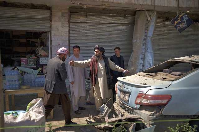 Taliban fighters and residents gather at the site of an explosion in Kabul, Afghanistan, Saturday, September 18, 2021. A sticky bomb exploded in the capital Kabul wounding a few people, said police officials. (Photo by Felipe Dana/AP Photo)